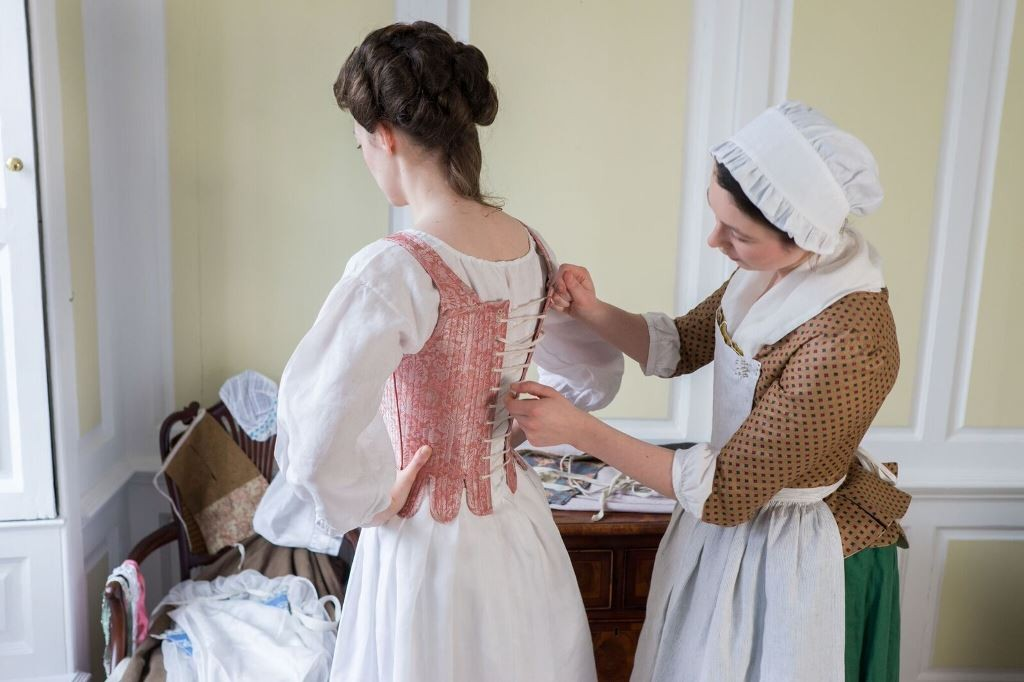 Kate Loven and Amy Bevan demonstrating the layers of 18th century clothing.